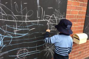 child drawing on blackboard