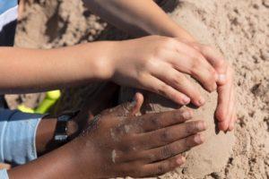 kids hands making sand castle